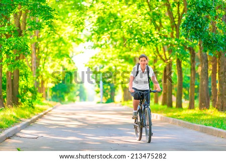 young girl on a bicycle in a park in the early morning  - stock photo