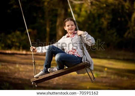 Young girl on an old wooden swing - stock photo