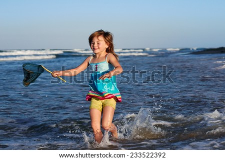 Young girl on beach holiday vacation with fishing net having fun - stock photo