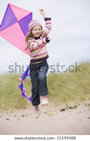 Young girl on beach with kite smiling - stock photo