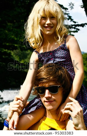 young girl on big brothers shoulders on a sunny day - stock photo