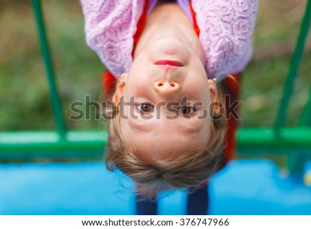 Young Girl On Climbing Frame In Playground - stock photo