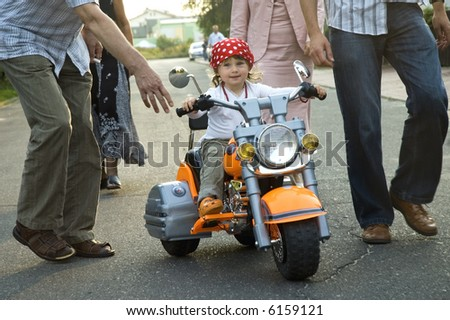 young girl on motor-bike on the playground - stock photo