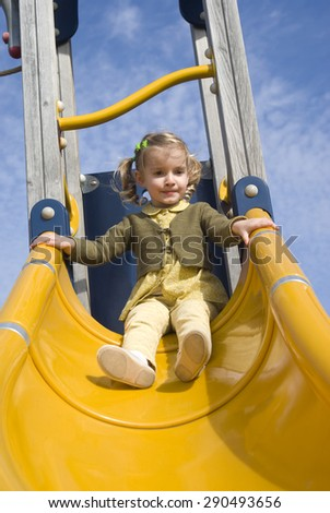 Young girl on slide in playground