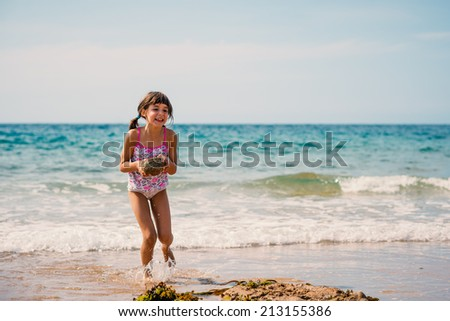 Young girl on the beach portrait holding rock. - stock photo