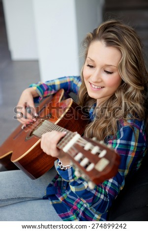 Young girl on the couch playing guitar - stock photo