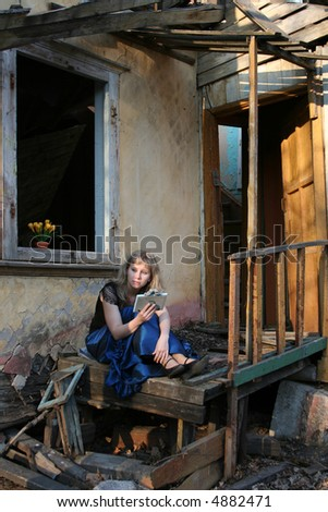 young girl on the doorstep of wrecked house