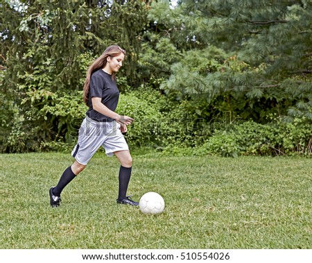 Young girl on the grass kicking a soccer ball and smiling