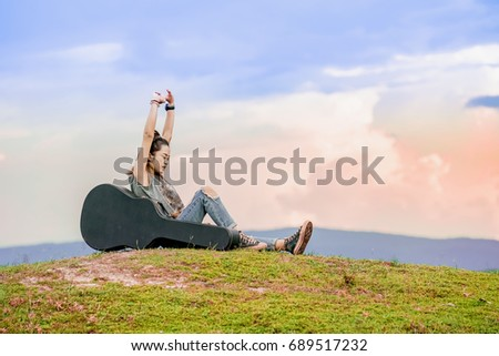Young girl on top of a mountain with a guitar