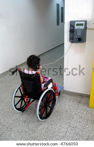 Young girl on wheelchair making a phone call - stock photo