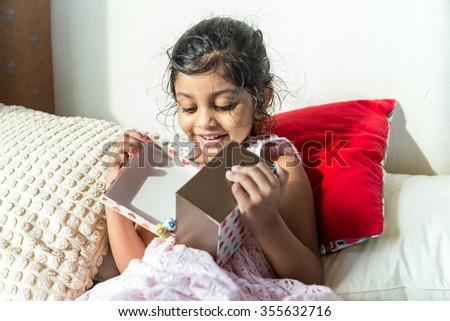 Young girl open up with present box - stock photo
