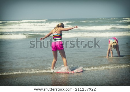 Young girl or teen learning to ride a skimboard on the Oregon coast. - stock photo
