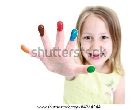 Young girl out of focus showing fingers of different color finger paint in focus - stock photo
