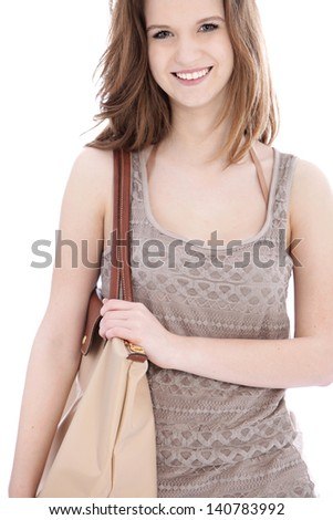 Young girl out shopping with a large cloth bag over her shoulder and a delightful smile isolated on white