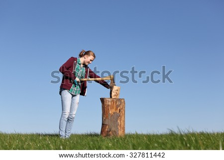 Young girl outdoors chopping wood with blue sky - stock photo