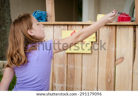 Young girl painting a lemonade stand sign