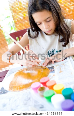 Young girl painting a paper plate in arts and craft. - stock photo