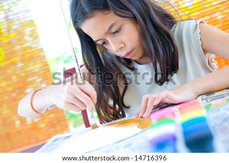 Young girl painting a paper plate with poster paint and wooden brush - stock photo