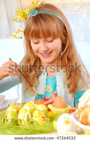 young girl painting easter eggs by the table
