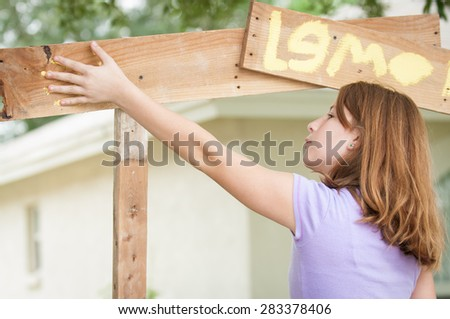 Young Girl Painting Lemonade Stand Places Her Hand, Covered In Yellow Paint,  On The