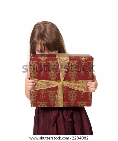 Young Girl Peeking From Behind Christmas Gift - stock photo