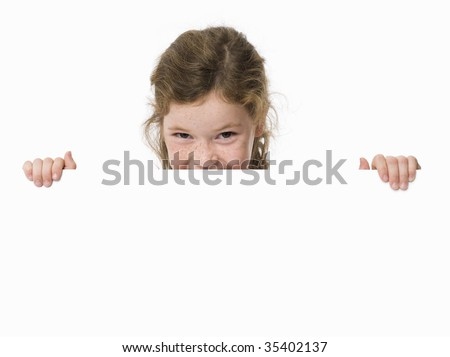 Young girl peeking over white sign - stock photo