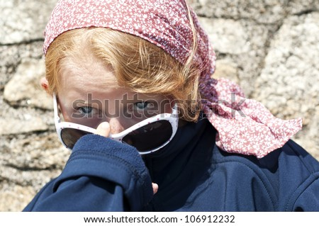 Young girl peers out from under sunglasses - stock photo