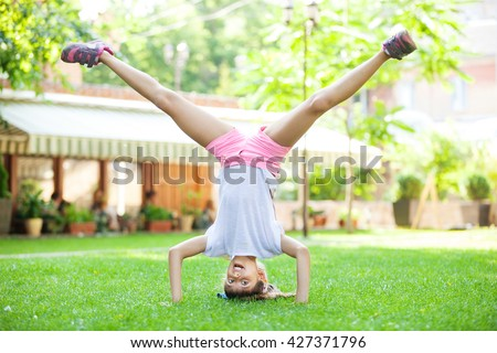 Young girl performing headstand in park - stock photo
