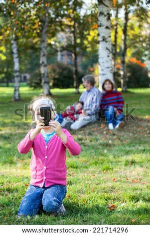 Young girl photographing with cellphone, family sitting on grass on background - stock photo