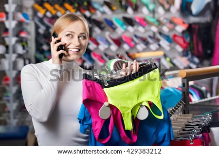 Young girl picking a sport bra in the shop while talking to the phone - stock photo