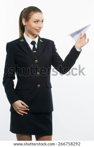 young girl pilot holding a paper airplane on light background