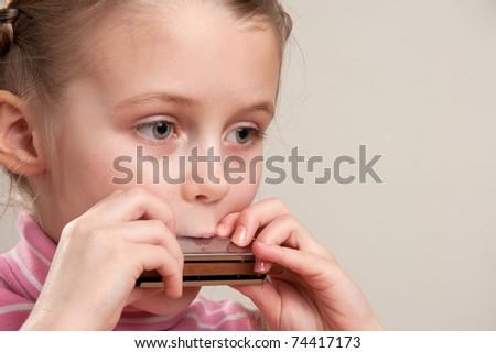 Young girl play blues harmonica - stock photo
