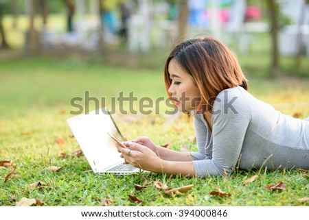 Young girl play mobile phone with laptop in garden