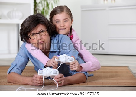 Young girl playing a video game with her grandmother - stock photo