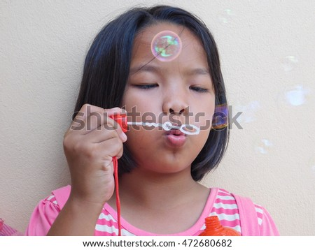 young girl playing blowing bubble