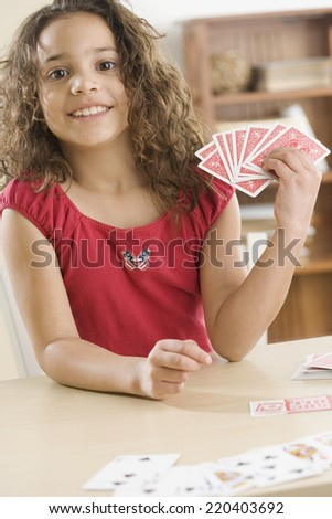 Young girl playing cards - stock photo