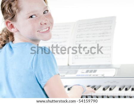 Young girl playing electric piano - stock photo