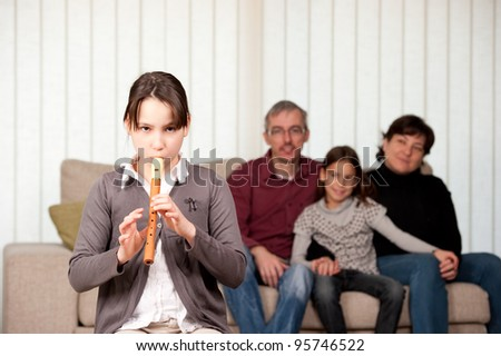 young girl playing flute with her family at home