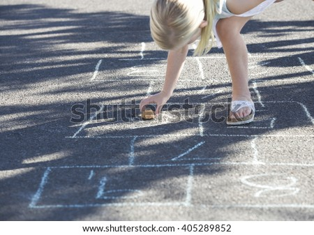 Young girl playing hopscotch - stock photo