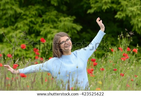 Young girl playing in a poppy field - stock photo