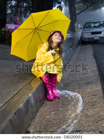 Young girl playing in rain 4 - stock photo