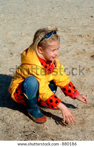 young girl playing in sand at lake in winter