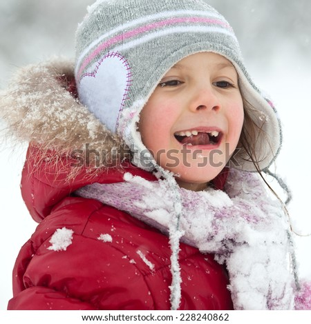 Young girl playing in the snow.  - stock photo