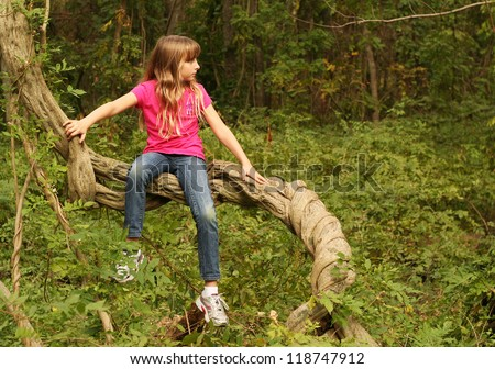 Young girl playing on a tree with room for your text - stock photo