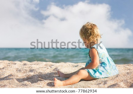 young girl playing on sand beach