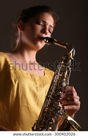 young girl playing on saxophone on dark background
