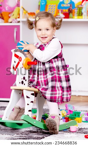 Young girl playing on wooden horse  - stock photo