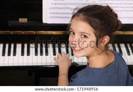 Young girl playing piano - stock photo