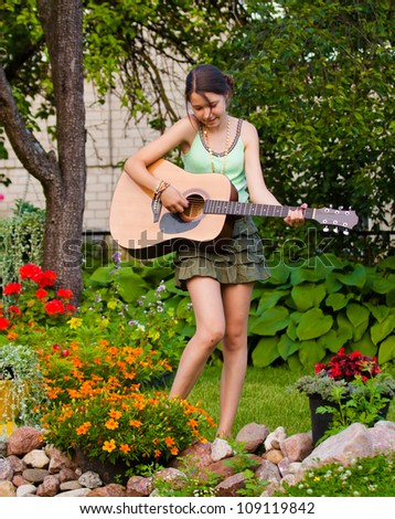 Young girl playing the guitar and singing in the garden - stock photo