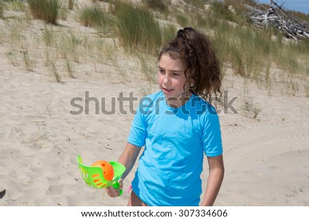 Young girl playing with a ball on the beach - stock photo